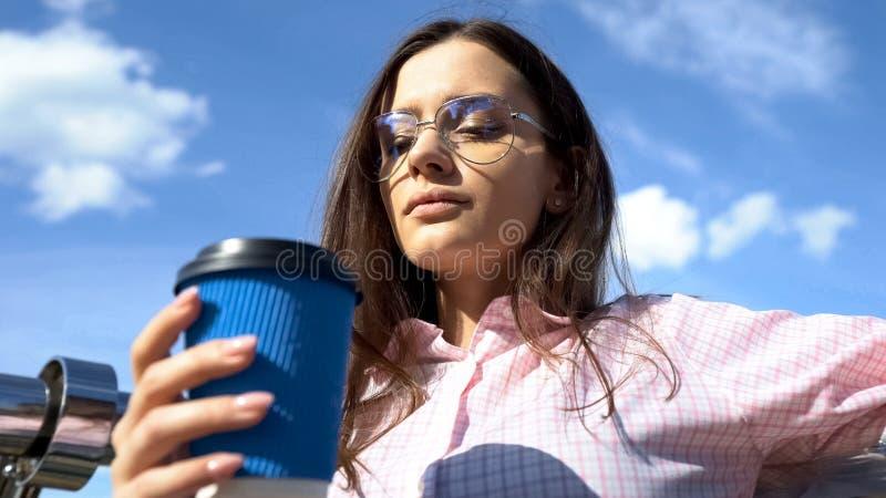 有咖啡纸杯的可爱的妇女享受寂寞,在工作前的孑然的 免版税库存照片