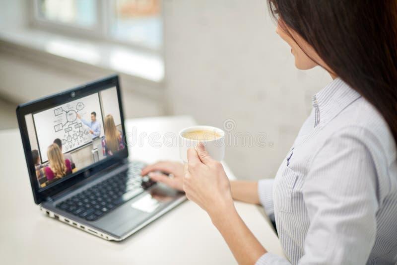 有咖啡观看的妇女webinar在膝上型计算机 库存图片
