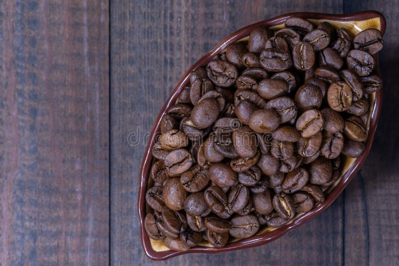 有咖啡豆的杯在木上面 免版税库存照片