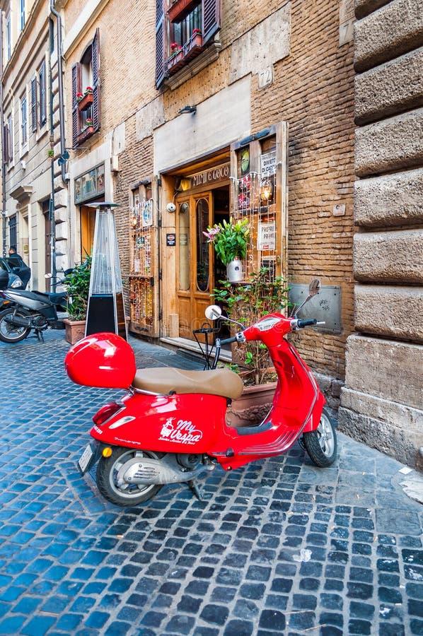 有咖啡馆的,小企业舒适狭窄的古老中世纪奥尔德敦铺路石街道,在罗马停放了红色葡萄酒脚踏车, 免版税图库摄影
