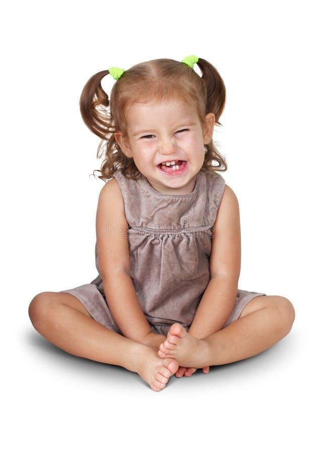 有咧嘴的恼怒的儿童女孩画象被隔绝坐白色 库存照片