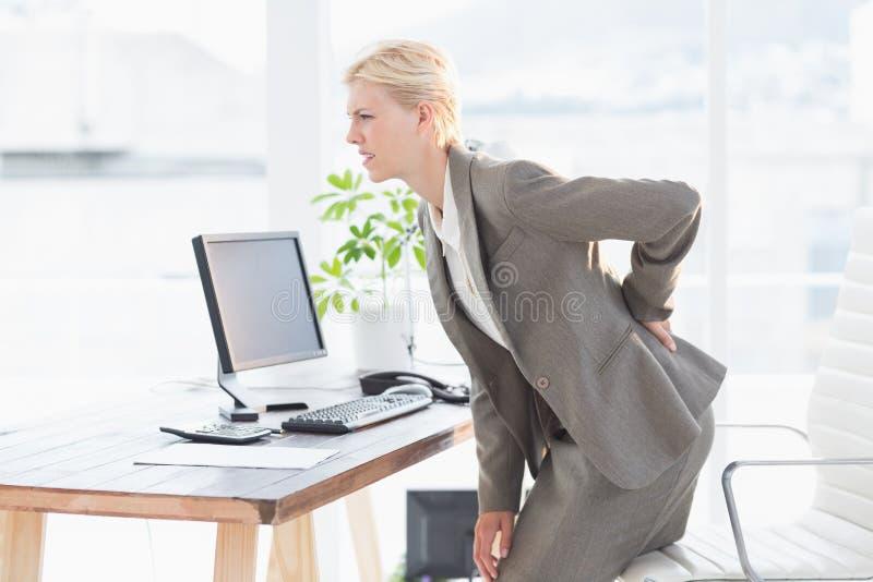 有哀伤的女实业家背部疼痛 免版税库存照片