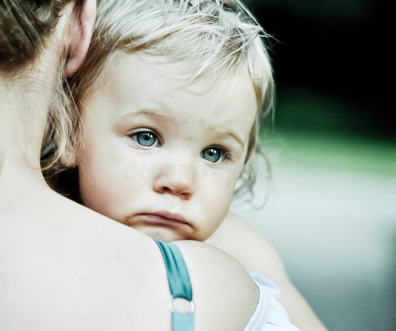 有哀伤的神色的小女孩在母亲的肩膀 库存照片