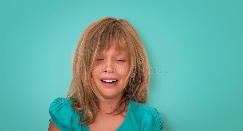 有哀伤的表示和泪花的小女孩 绿松石背景的哭泣的孩子 情感 免版税图库摄影
