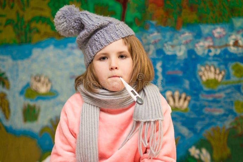 有哀伤的面孔的病的在嘴穿戴的女孩和温度计在围巾 免版税库存图片