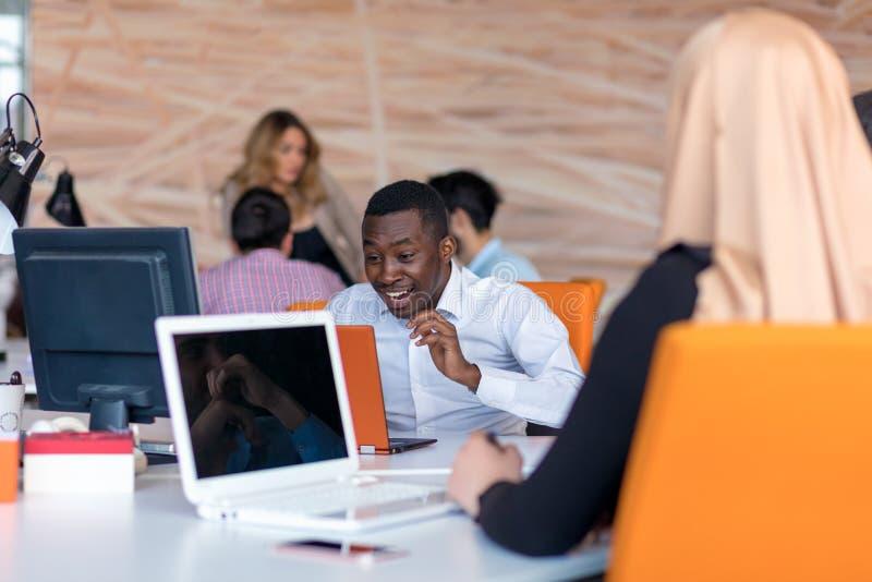 有哀伤的鬼脸的沮丧的年轻非洲企业家在他的膝上型计算机前面在办公室 免版税图库摄影