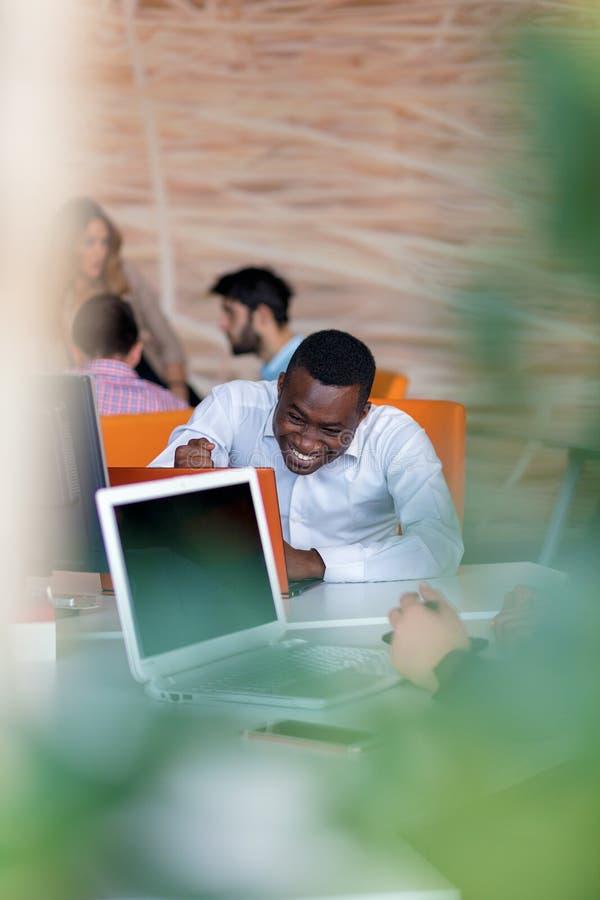 有哀伤的鬼脸的沮丧的年轻非洲企业家在他的膝上型计算机前面在办公室 免版税库存图片
