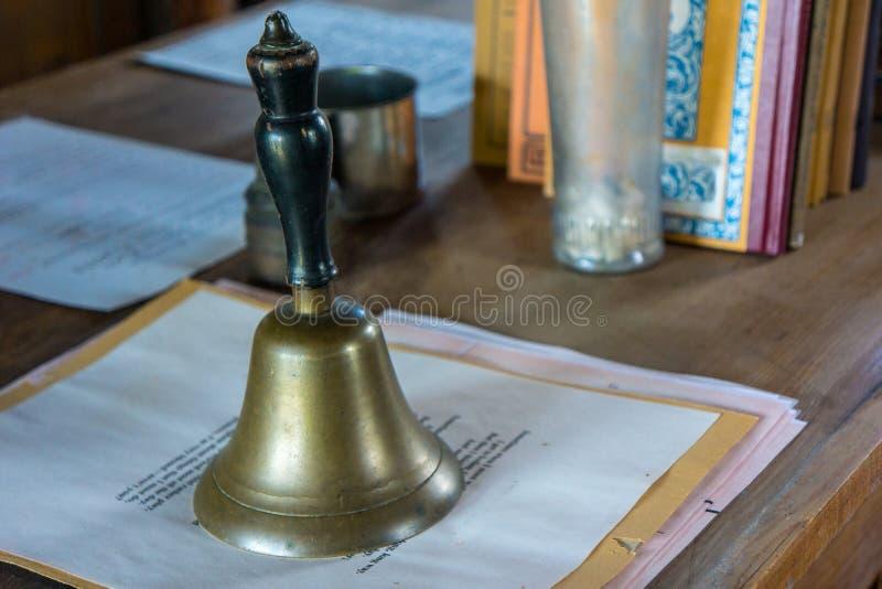 有响铃、书和纸的减速火箭的老师书桌 库存照片