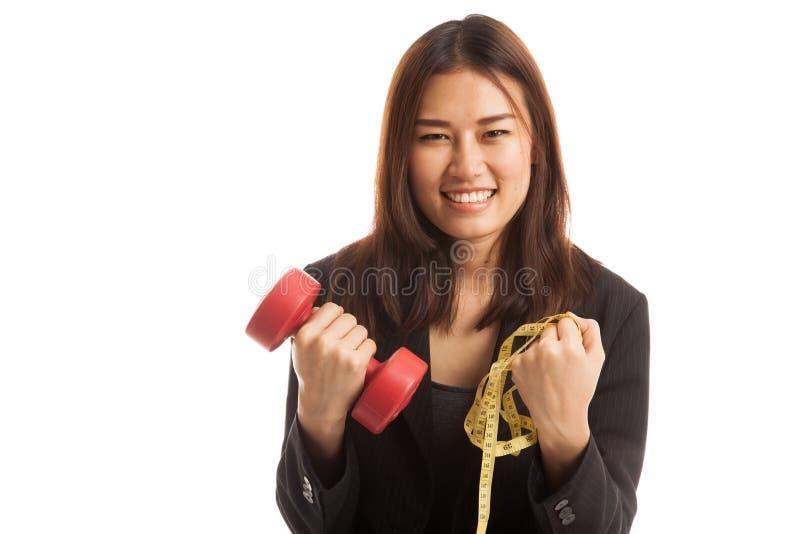 有哑铃和测量的磁带的健康亚裔女商人 库存照片