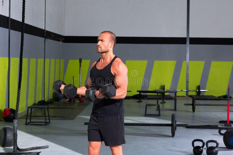 有哑铃执行crossfit的健身房人 库存图片
