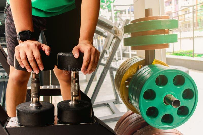 有哑铃的亚裔人爱好健美者衡量力量英俊的运动锻炼 隐喻健身和锻炼概念锻炼健康 库存图片