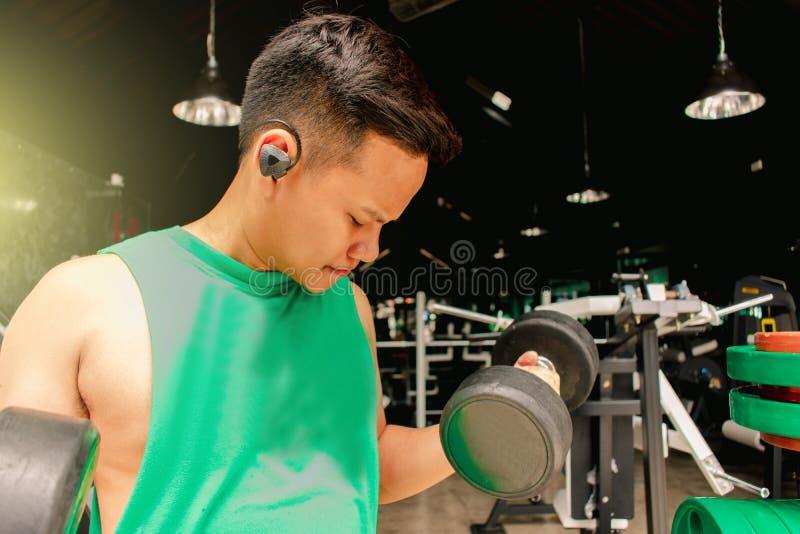 有哑铃的亚裔人爱好健美者衡量力量英俊的athle 免版税库存照片