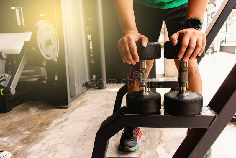 有哑铃的亚裔人爱好健美者衡量力量英俊的athle 库存图片