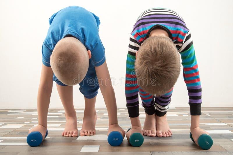 有哑铃的儿童火车 体育的概念在家庭的 库存照片