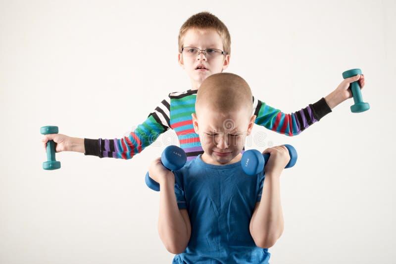 有哑铃的儿童火车 体育的概念在家庭的 免版税库存照片