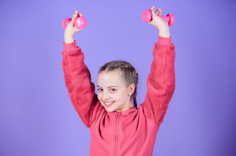 有哑铃的愉快的儿童运动员 小女孩举行哑铃锻炼  ??muscules? ?? 免版税图库摄影