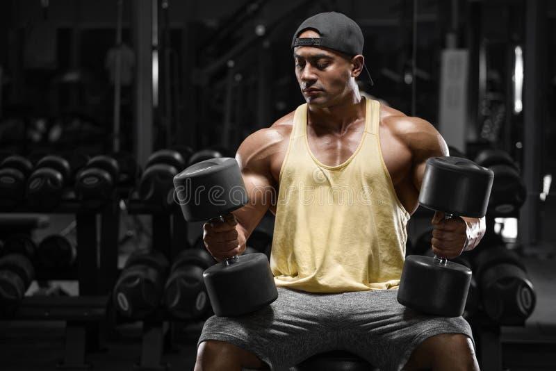 有哑铃的肌肉人解决在健身房,强的阿拉伯爱好健美者男性的 免版税库存图片