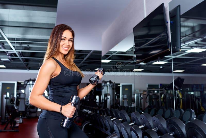 有哑铃的运动的女孩在健身房 体育运动 库存照片