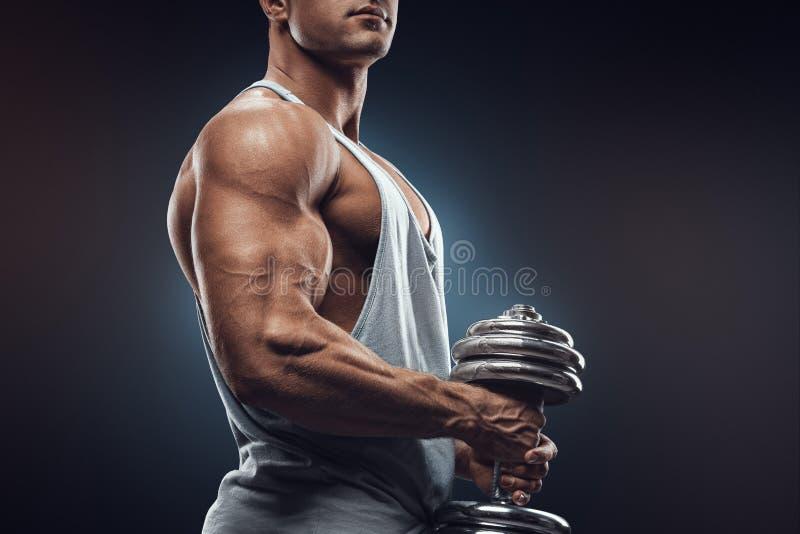 有哑铃的年轻人准备对屈曲在黑暗的bac的肌肉 免版税库存图片