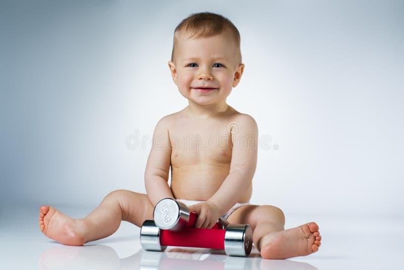 有哑铃的婴孩 免版税库存照片