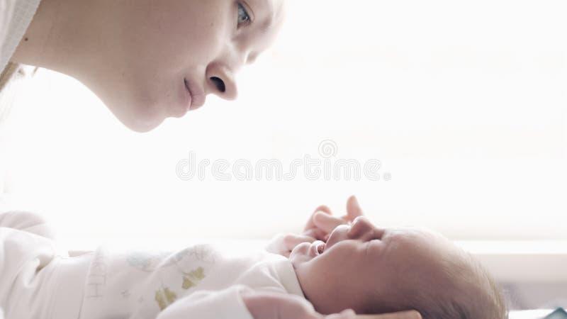 有哭泣的婴孩的美丽的年轻母亲 图库摄影