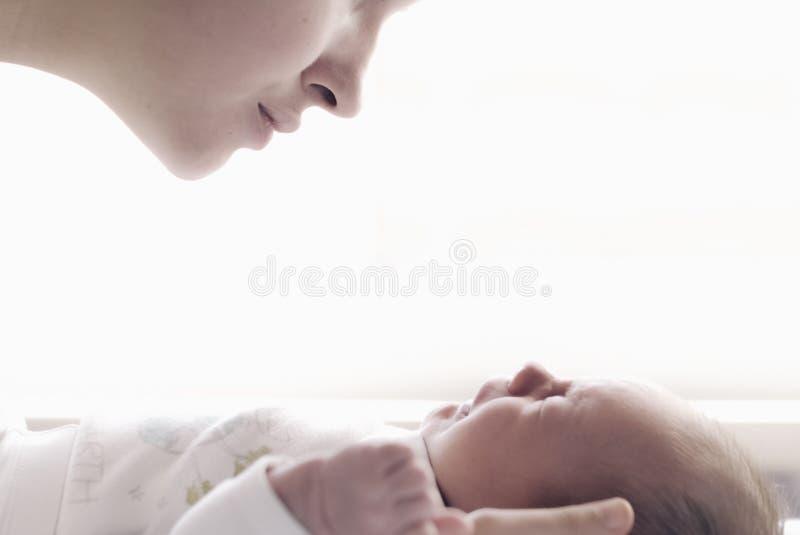 有哭泣的婴孩的美丽的年轻母亲 库存照片
