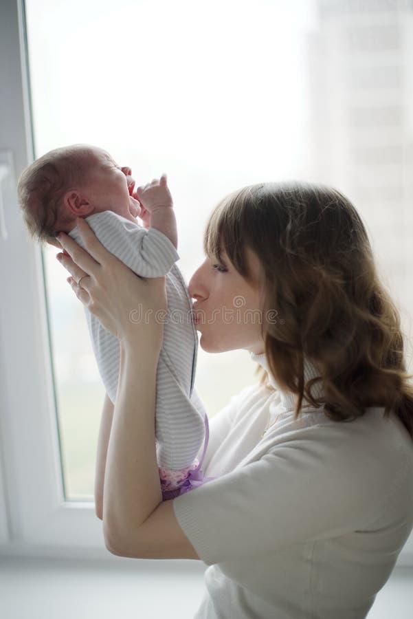 有哭泣的婴孩的年轻母亲 库存图片
