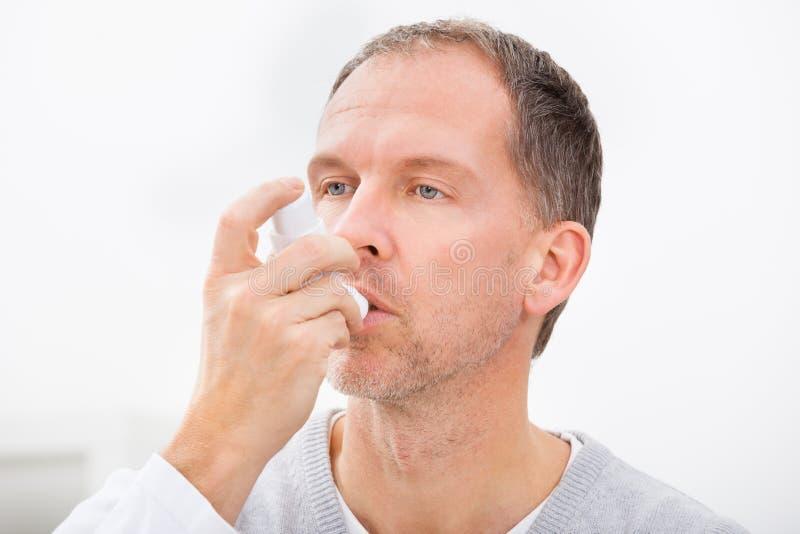 有哮喘吸入器的人 免版税库存图片