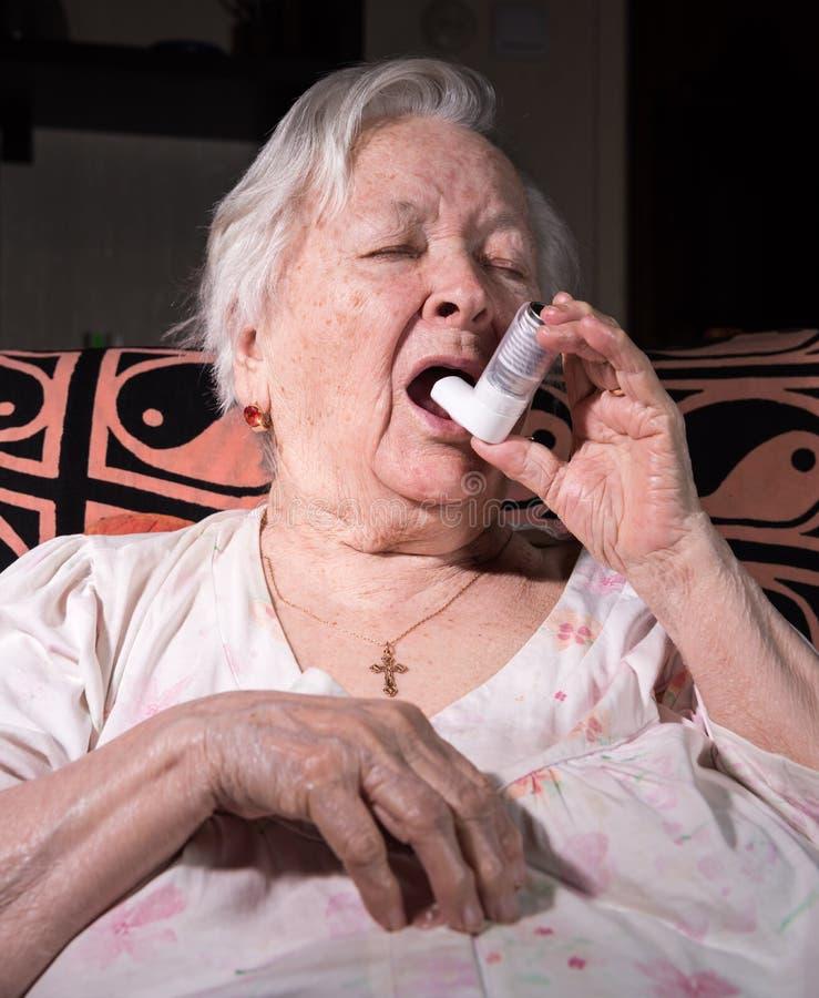 有哮喘吸入器的老病的妇女 免版税图库摄影