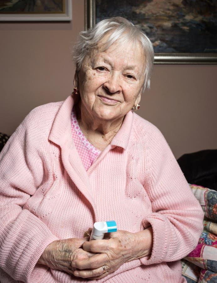 有哮喘吸入器的老病的妇女 免版税库存照片