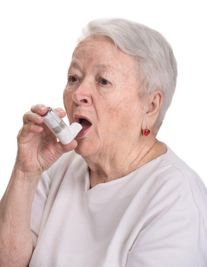有哮喘吸入器的资深妇女 免版税图库摄影