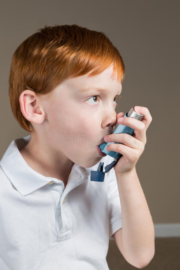 有哮喘的小男孩使用他的吸入器 免版税库存图片