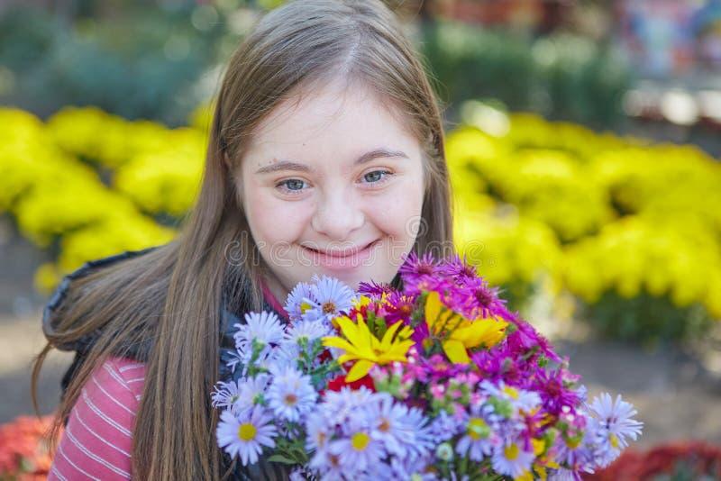 有唐氏综合症的女孩在秋天公园 免版税图库摄影