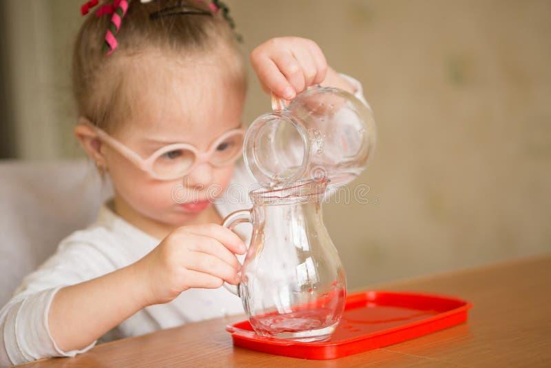 有唐氏综合症的女孩轻轻地倾吐从水罐的水入水罐 库存图片
