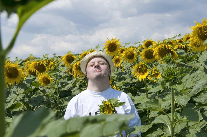 有唐氏综合症的年轻人休息和愉快作为在开花的领域的太阳 免版税库存照片