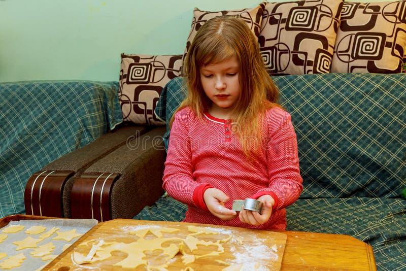 有唐氏综合症的愉快的女孩烘烤曲奇饼 免版税库存照片