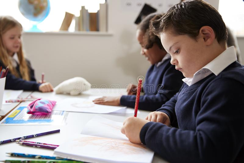 有唐氏综合症的青春期前的男生坐在书桌赞扬在小学类,关闭的,侧视图 免版税库存照片