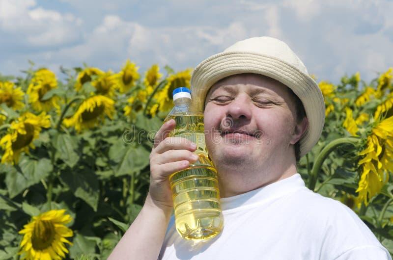 有唐氏综合症藏品瓶的人新鲜的向日葵油 有新收获的愉快的农夫 免版税库存照片