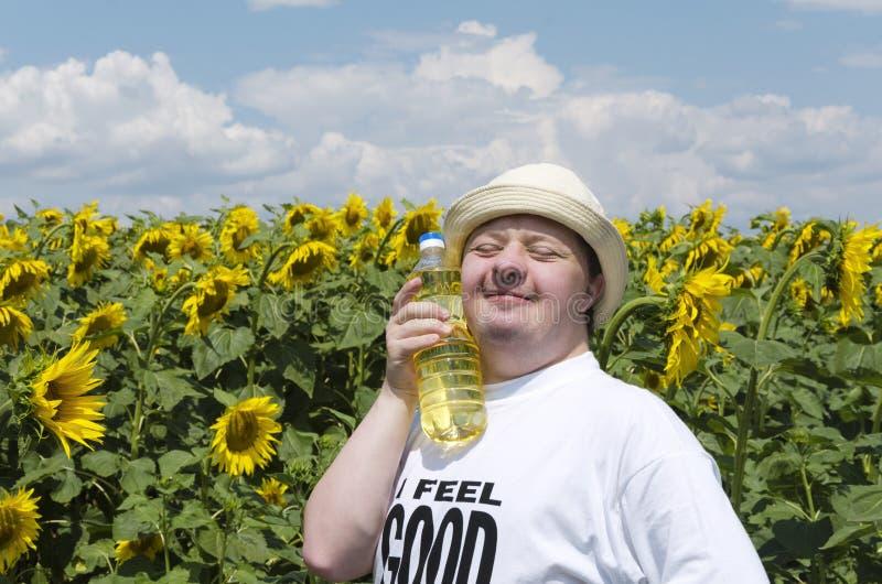 有唐氏综合症whio的微笑和年轻人满意对向日葵油 免版税库存照片
