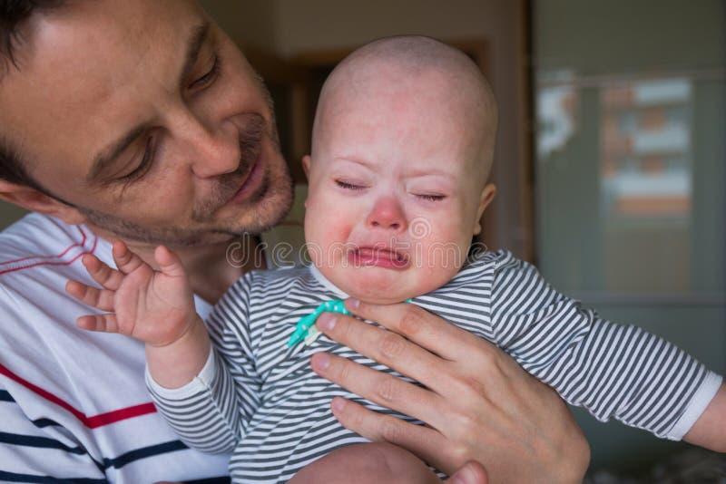 有唐氏综合症哭泣的逗人喜爱的男婴 免版税库存照片