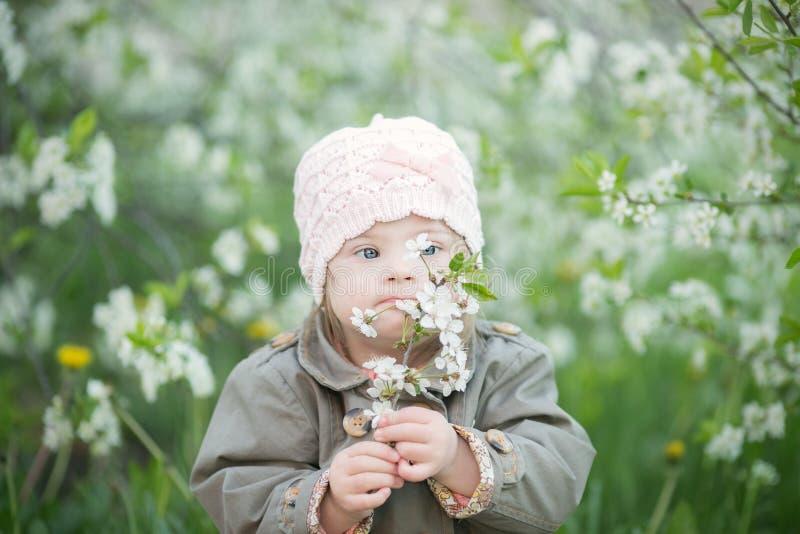 有唐氏综合症嗅到的花的小女孩 免版税库存图片
