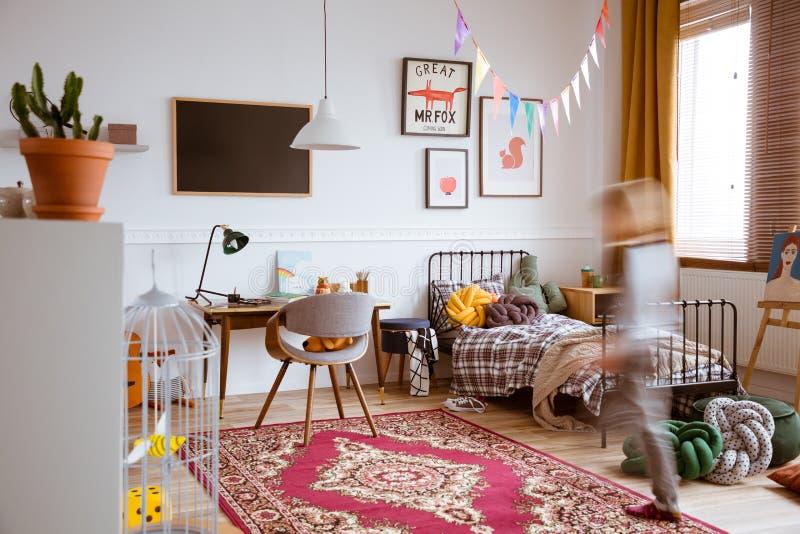 有唯一金属床、木书桌和设计扶手椅子的孩子减速火箭的卧室 库存图片