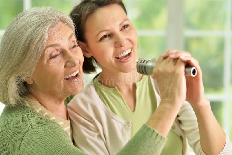 有唱歌在话筒的女儿的资深妇女 库存图片