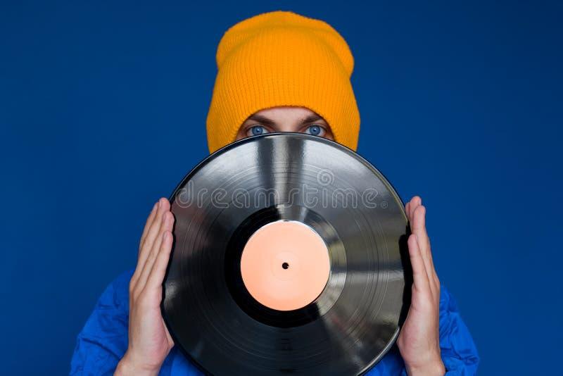 有唱片,人的一个蓝色体育90s样式夹克和黄色帽子的人掩藏他的面孔在乙烯基圆盘下 免版税库存图片