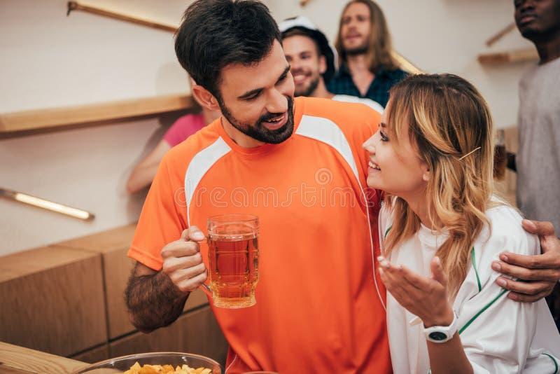 有啤酒拥抱的女朋友的微笑的人 免版税库存图片