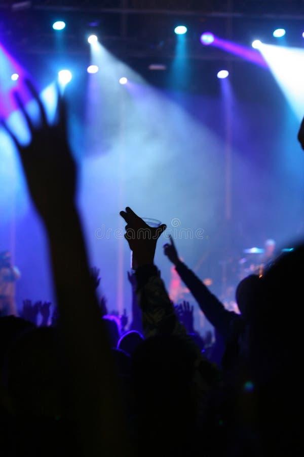有啤酒杯的手在音乐会的天空中 免版税库存照片