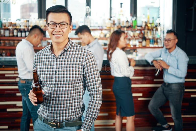有啤酒瓶的亚裔人在与朋友的酒吧 免版税图库摄影