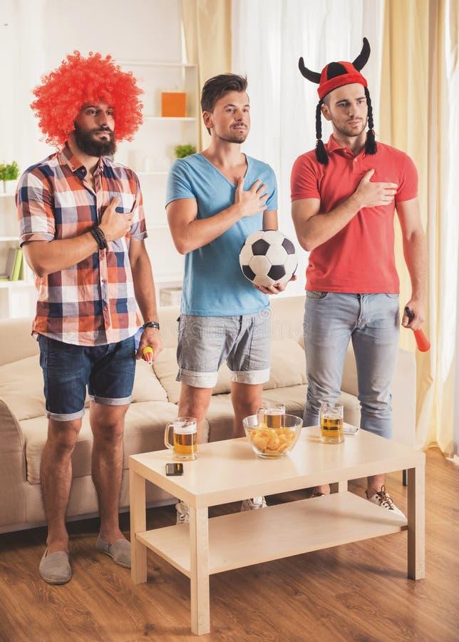 有啤酒观看的橄榄球的年轻人在家 库存图片
