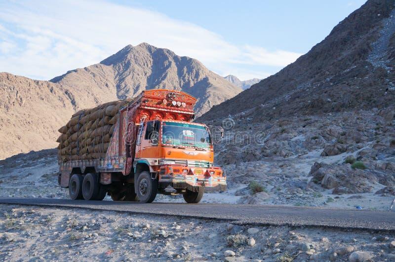 有喀喇昆仑山脉山脉的装饰老卡车在后面 库存照片