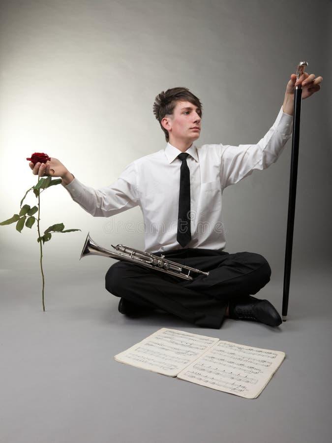 有喇叭、红色玫瑰和藤茎的年轻男孩 免版税图库摄影